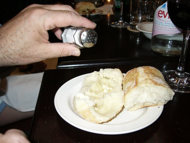 A kindred spirit salts the sweet butter spread on the delicious warm dinner rolls at Le Select.
